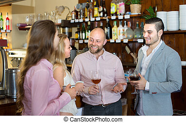 Group of cheerful young adults chatting in bar with drinks. Selective focus.