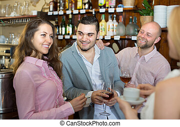 Group of cheerful young adults hanging out in bar. Focus on guy