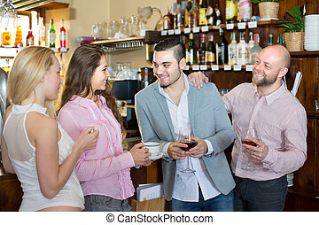 Group of happy smiling young adults hanging out in bar with beverages.