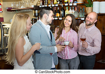 Group of smiling positive young adults hanging out in bar with drinks.