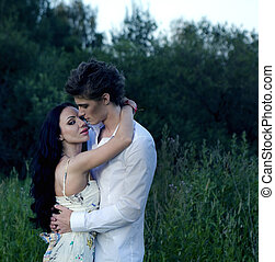 Young adults in love - young couple on nature background -...