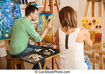 Young adults painting at an art school - Rear view of a...