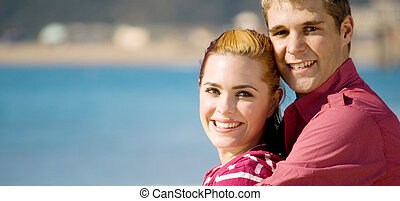 young adults - young couple on beach together hugging