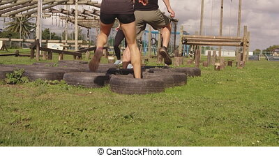 Young adults training at an outdoor gym bootcamp - Rear view...