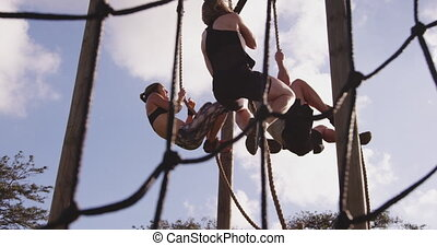 Young adults training at an outdoor gym bootcamp - Side view...