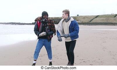 Young Adults Walking Along A Winter Beach - Two friends talk...