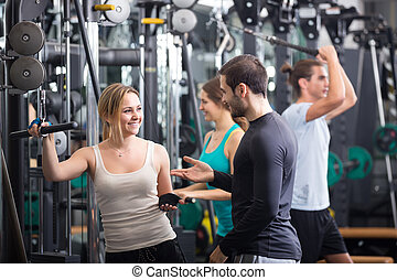 Young adults working out in fitness club.