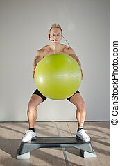 Young aerobics male coach on step with big ball teaching class