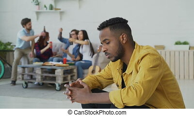 Young african amercan man feels upset and isolated while his friends celebrating party at home