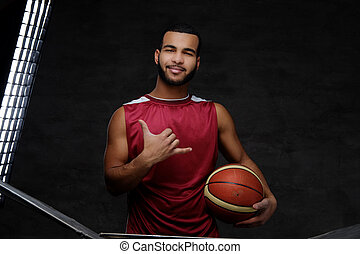 Young African-American basketball player in sportswear isolated over dark background.