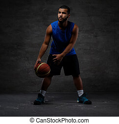 Young African-American basketball player in sportswear playing with ball. Isolated on a dark background.