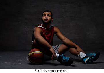 Young African-American basketball player in sportswear sitting on a floor with a ball on a dark background.