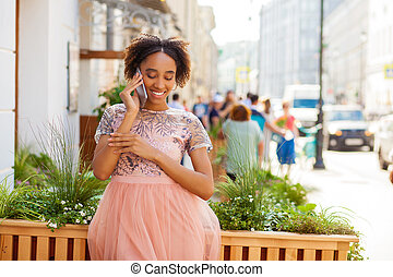 Young African American black woman in pink dress talking on cellphone
