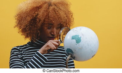 Young african american black woman looking at the globe through the magnifier