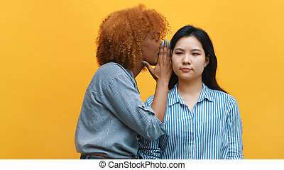 Young african american black woman whisperingto her asian friend