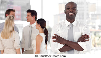 Business leader standing inf front of business team smiling