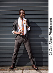 young african american businessman drinking coffee outdoors