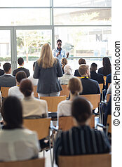Young African american businesswoman doing speech and answering questions in conference room