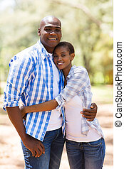 young african american couple hugging in forest