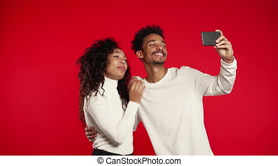 Young african american couple in white making selfie with smartphone on red studio background. Love, holidays, happiness concept.