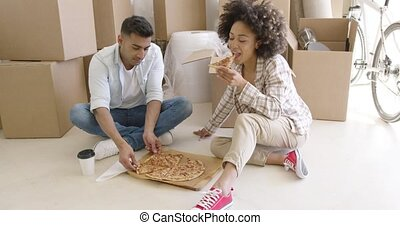 Young African American couple tucking into a pizza as they...