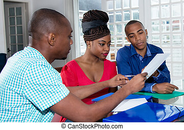 Young african american couple with contract of real estate agent