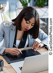young african american designer working with drawing tablet and laptop at office