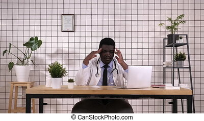 Young african american doctor suffering from headache...