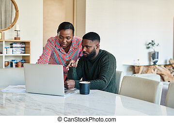 Young African American doing online banking together at home