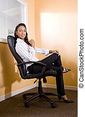 Young African-American female office worker sitting in chair