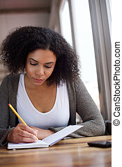 Young african american female student writing in book