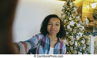 Young african american girl chatting online conversation using smartphone camera at home near Christmas tree