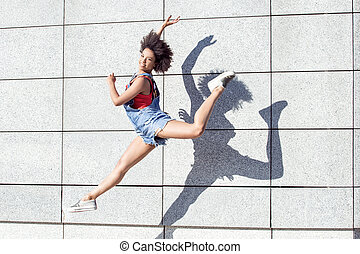 Young african american girl jumping.