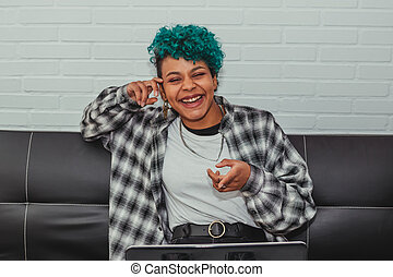 young african american girl looking at the computer sitting on the sofa