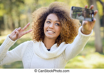 Young African American girl selfie in the park with a smartphone