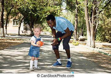 Young African American god father with little girl playing...