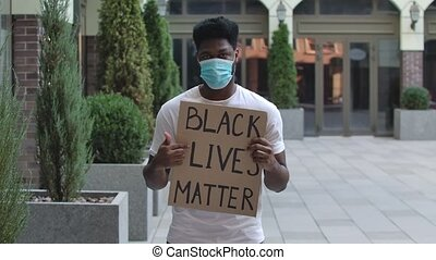 Young African American guy in a medical mask holds a cardboard poster that says Black Lives Matter. Demonstration against the police and racism. Slow motion. Close up portrait of a man outdoors