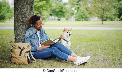 Young African American lady is reading book sitting on lawn in park and stroking her purebred pet dog with love and tenderness. Enjoying weekend with animals concept.