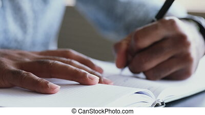 Close up young african american male student holding pen, writing notes in paper notepad. Confident mixed race businessman planning workday, noting daily cases in organizer before workday start.
