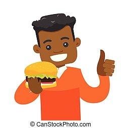 Young african-american man eating hamburger.
