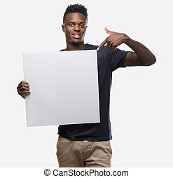 Young african american man holding a banner very happy pointing with hand and finger to the side