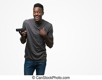 Young african american man holding a gun with surprise face pointing finger to himself