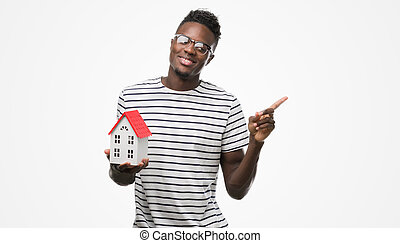 Young african american man holding house very happy pointing with hand and finger to the side