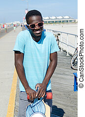Young African American man holding skateboard