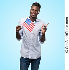 Young african american man holding USA flag very happy pointing with hand and finger to the side
