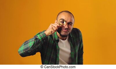 Young african american man looking through magnifying glass against yellow background. High quality FullHD footage