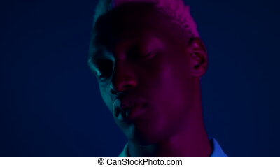 Young african american man moving head on dark blue background with pink neon light. Portrait of black guy with dyed white curly hairstyle. High quality 4k footage
