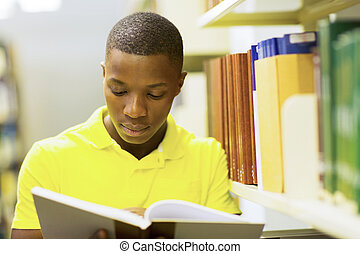 young african american man reading book in college library