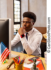 Young African American man sitting in the office