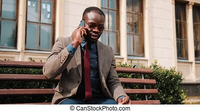 Young African American man sitting on a bench and talks on his smartphone. He talks to his business partner. Business and lifestyle concepts